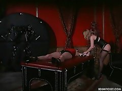 Girl is tied to the table and the mistress is having fun