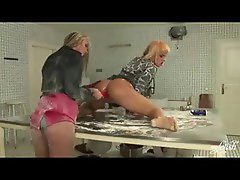 Two chicks in the kitchen using toys for pleasure