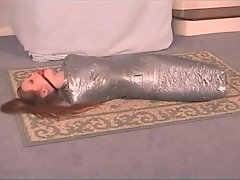 Mummified Restrain bondage Young lady In Silver Gauze
